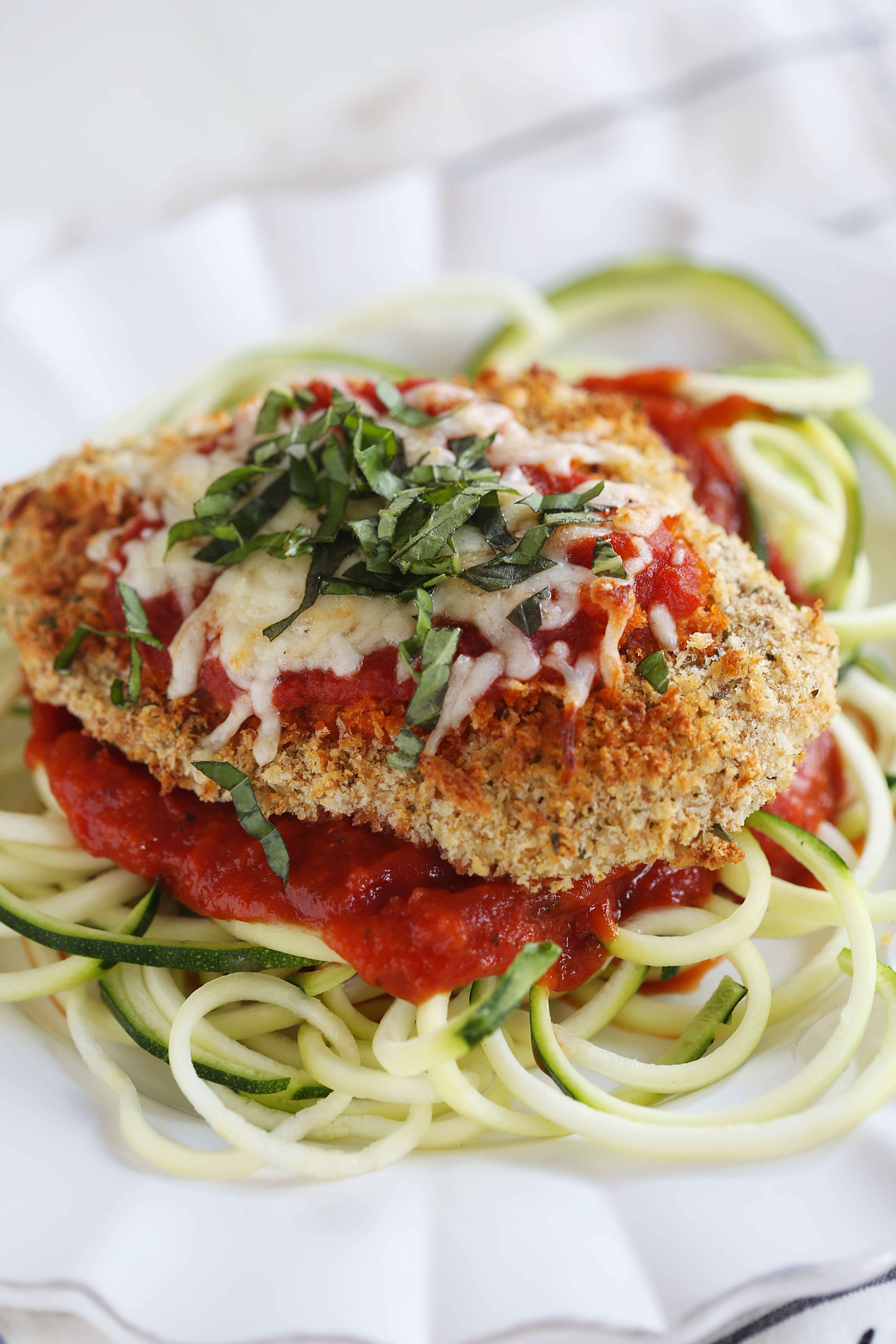 This recipe for Baked Chicken Parmesan with Zucchini Noodles is healthy, delicious and can easily be made in just 30 minutes or less!