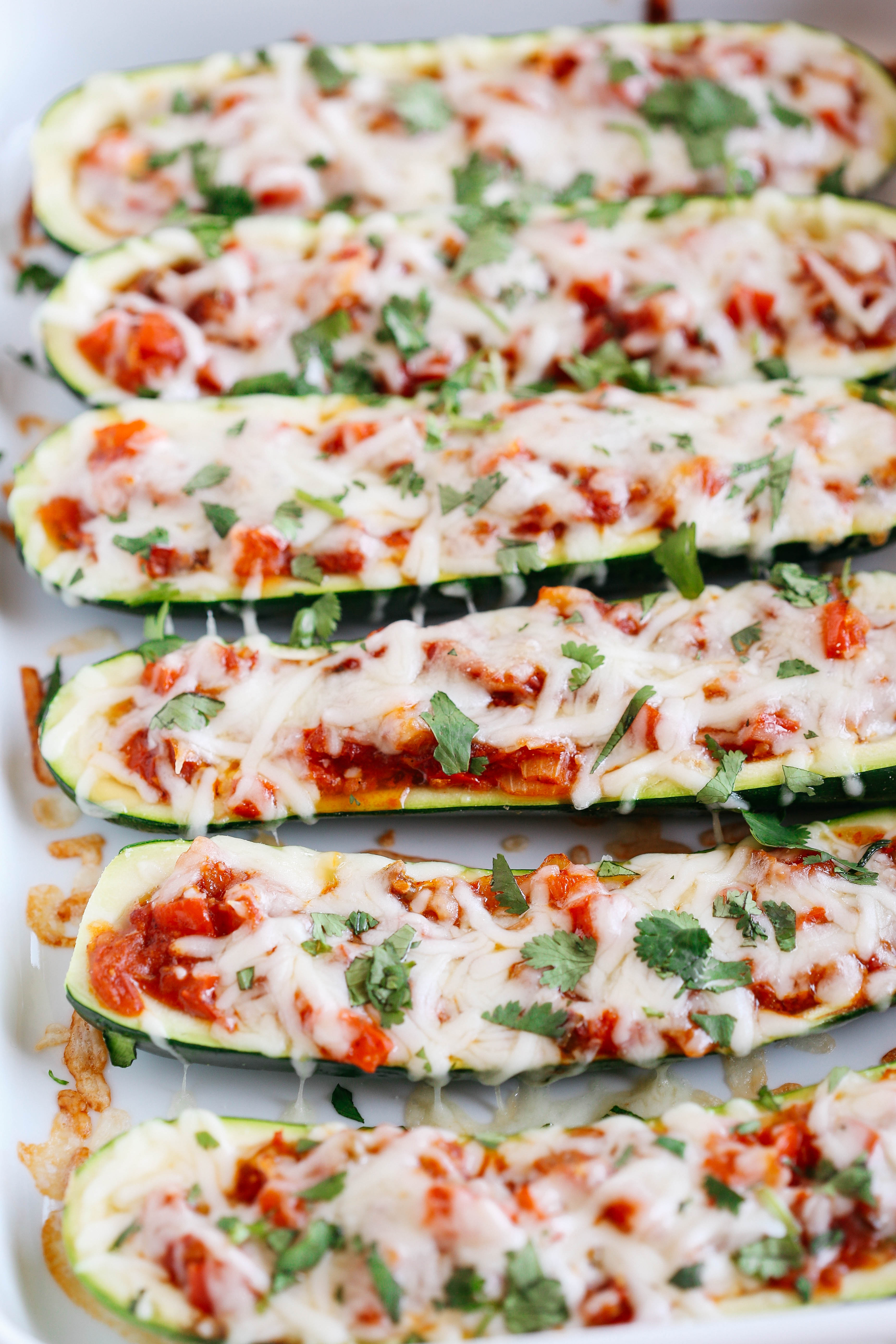 These Enchilada Stuffed Zucchini Boats are super flavorful, easy to make and are a much healthier alternative to your favorite dish!