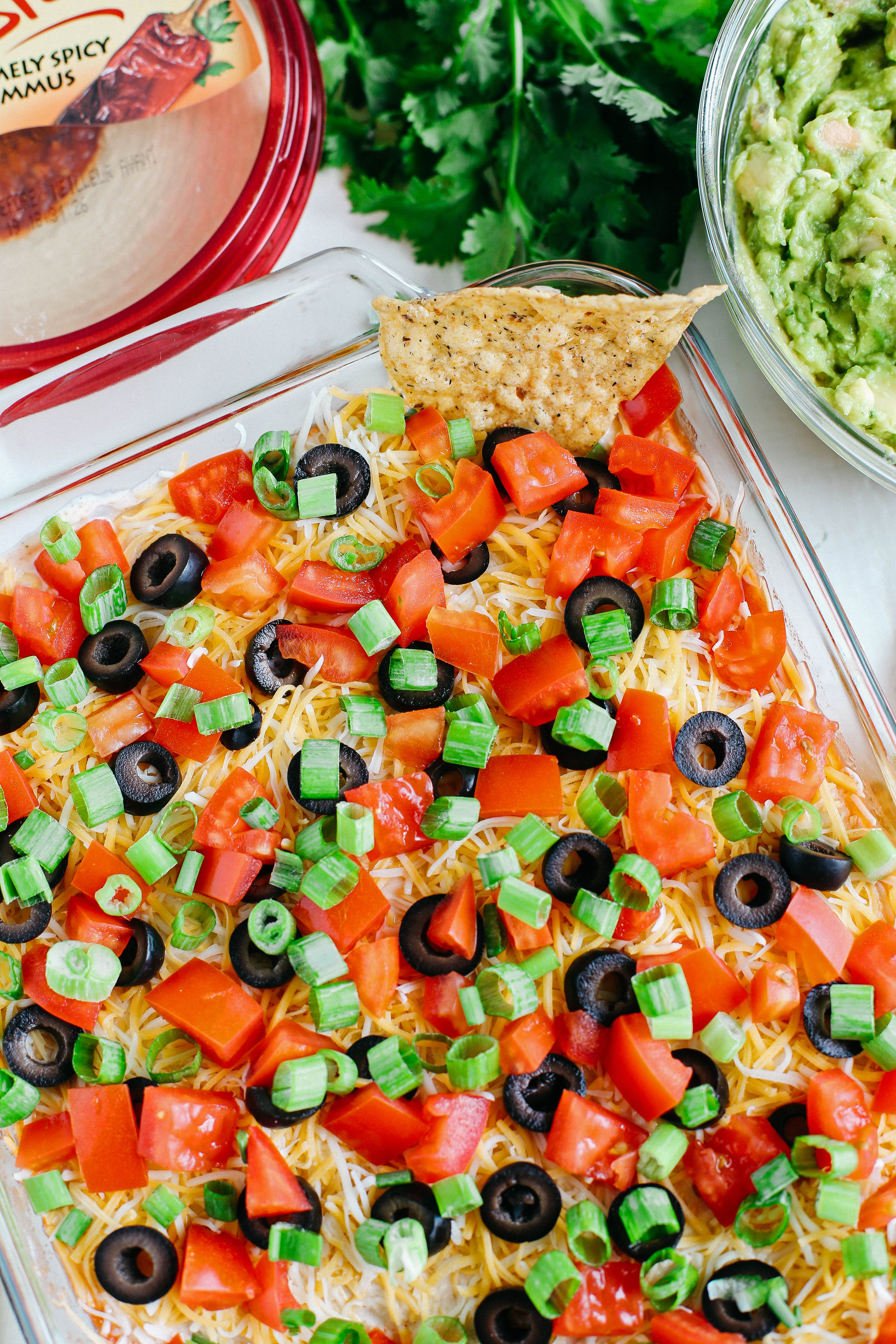 This Healthier 7 Layer Spicy Taco Dip is a lighter take on your favorite party appetizer perfect for any gathering or event that you can enjoy guilt-free!