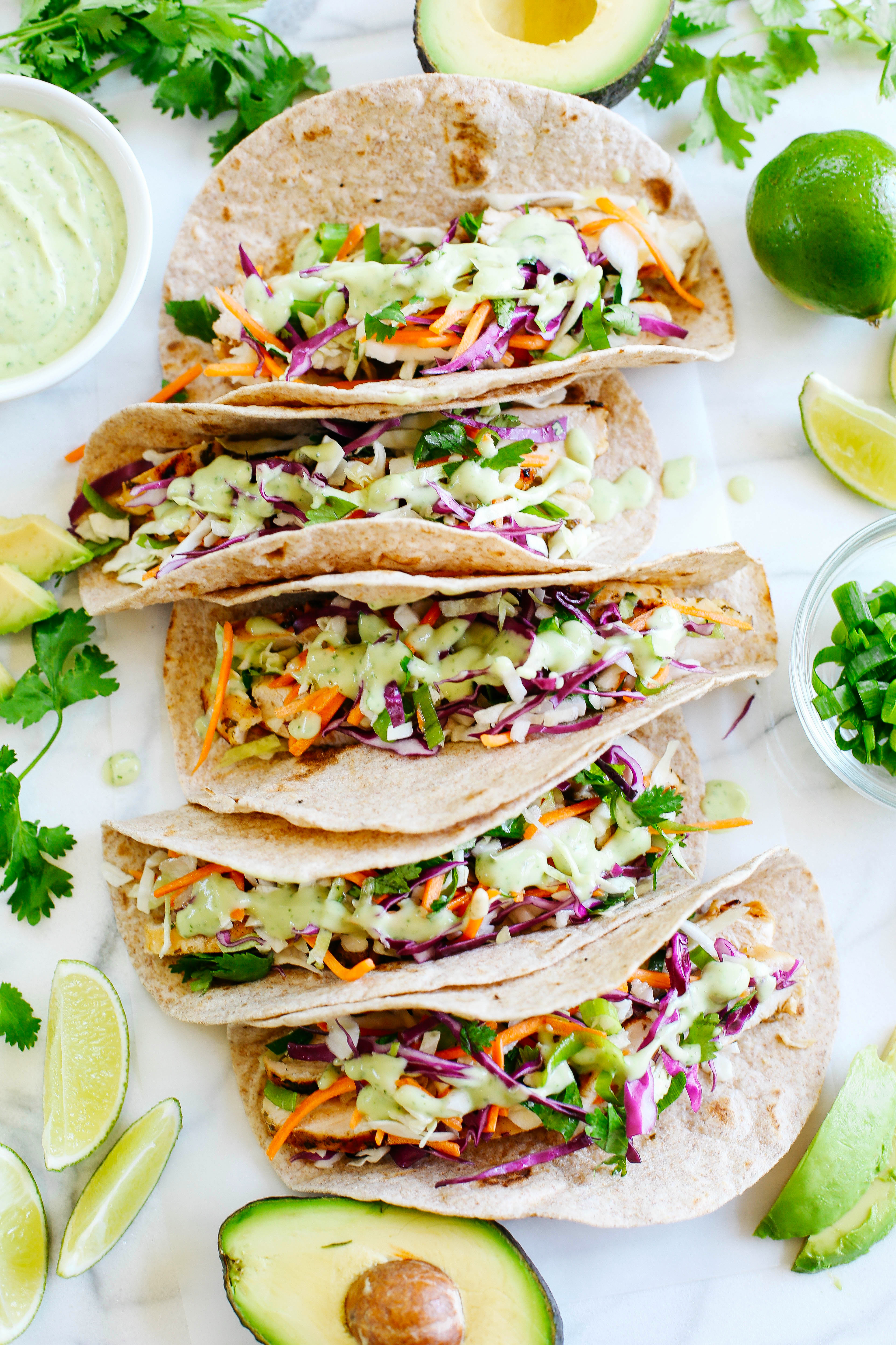 These Cilantro Lime Chicken Tacos with tangy coleslaw and avocado crema are simple, fresh and delicious making this the perfect EASY summer recipe!