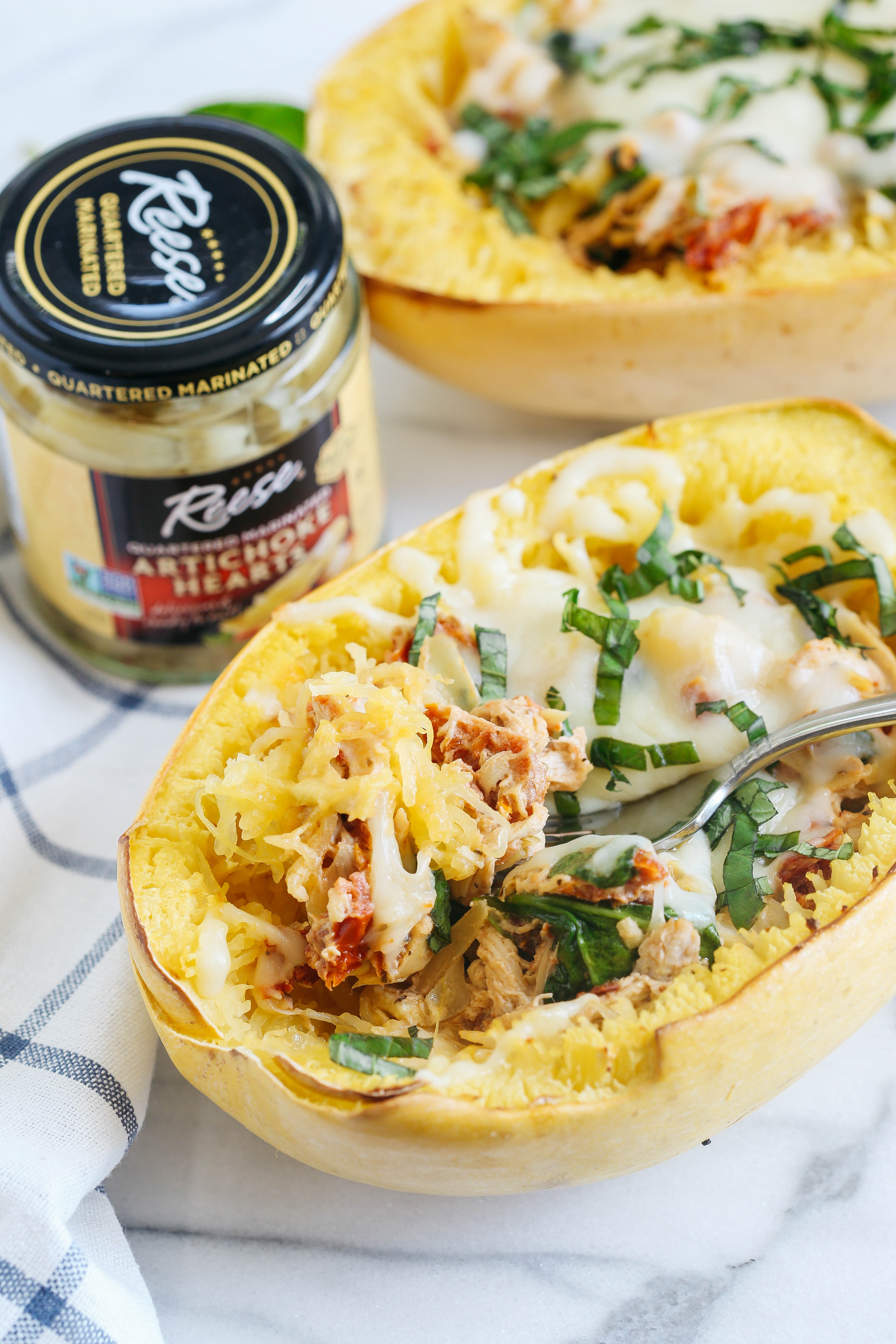 These Sun Dried Tomato and Artichoke Spaghetti Squash Boats are cheesy, delicious and make the perfect weeknight comfort meal that you can enjoy guilt-free!