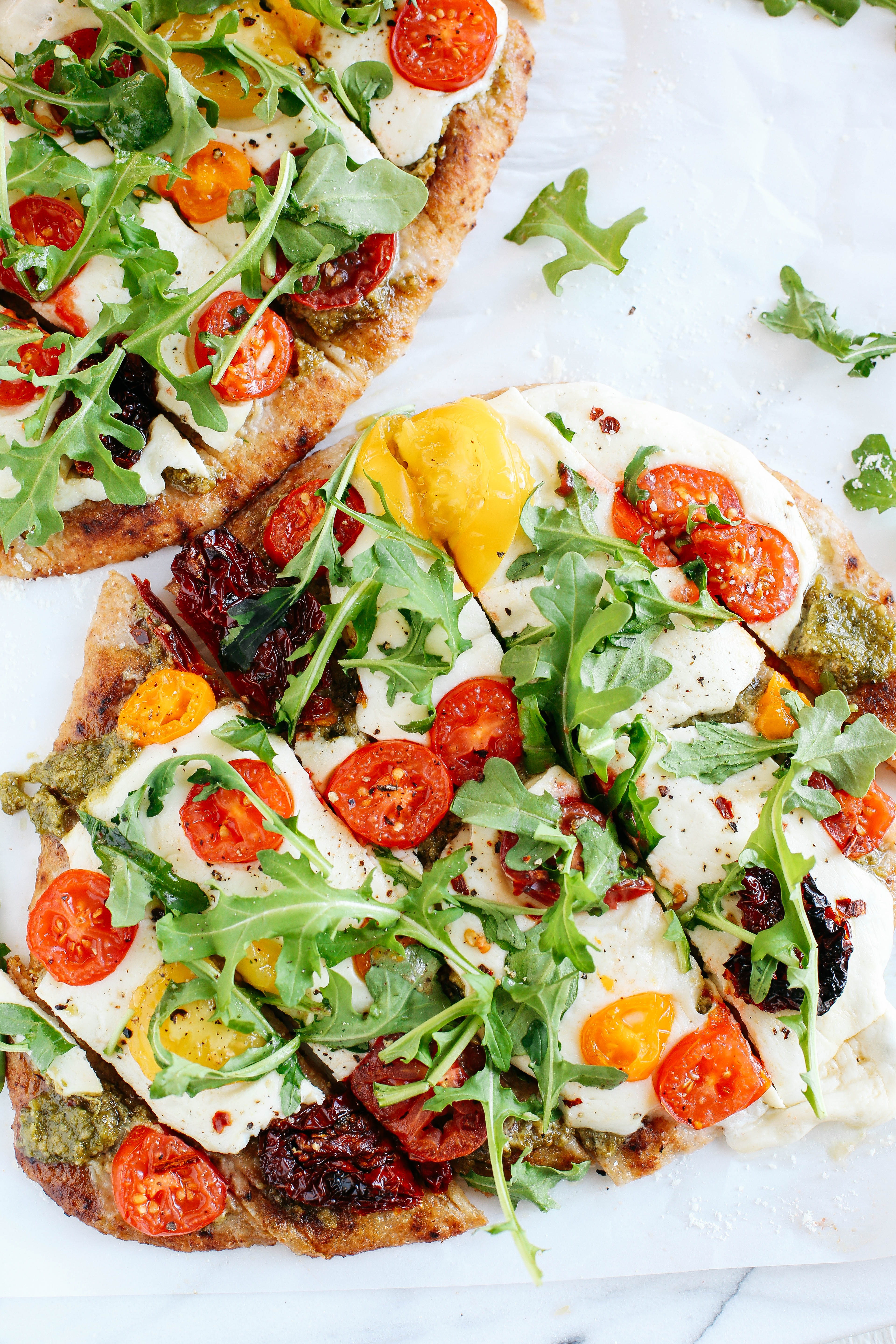 EASY garlicky pesto flatbread pizzas full of fresh tomatoes, basil and arugula for a flavorful weeknight dinner that can be ready in just 15 minutes!