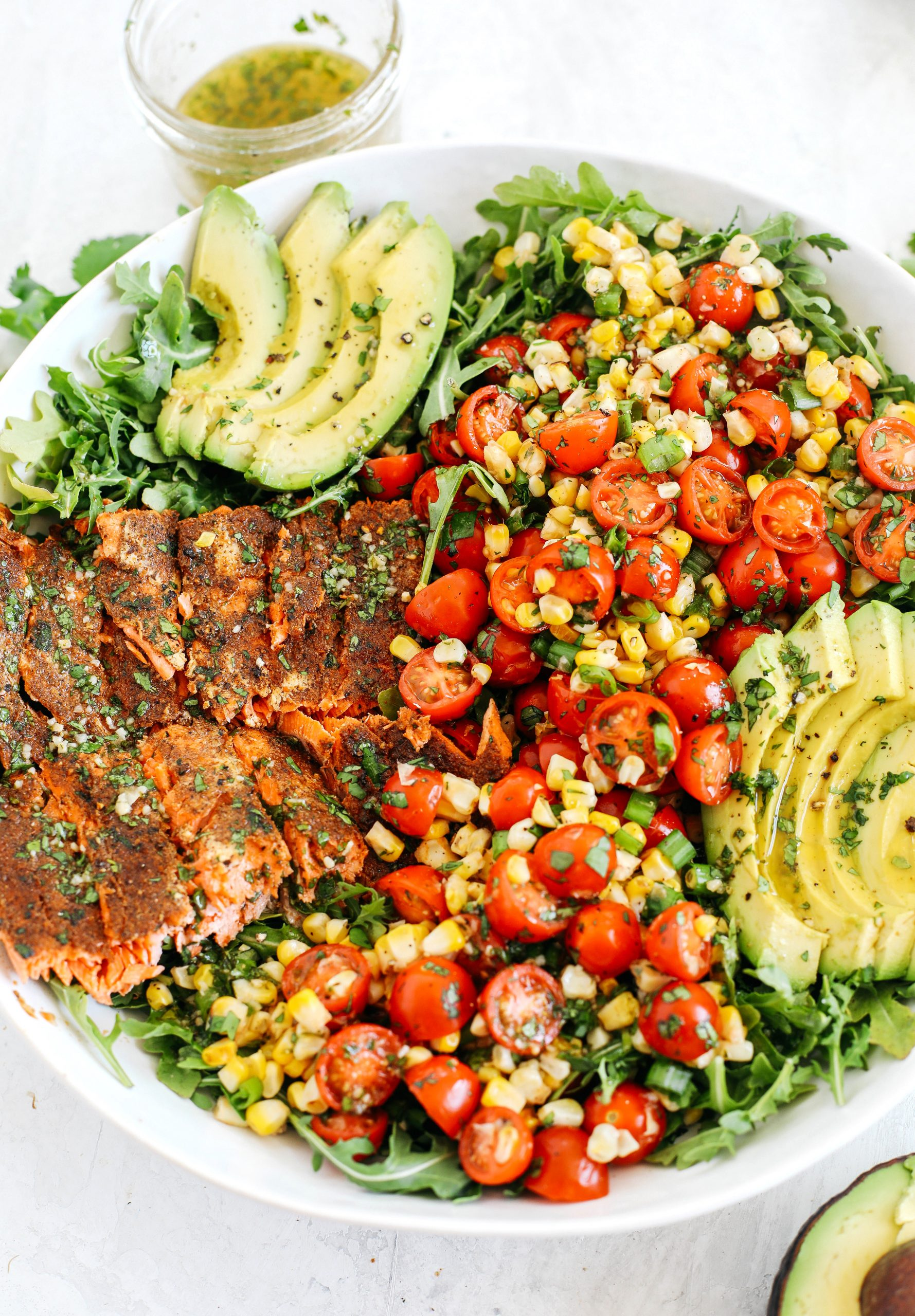 Chili-rubbed salmon with grilled corn, fresh tomatoes and sliced avocado all tossed together with a cilantro-lime dressing makes the perfect summer salad!