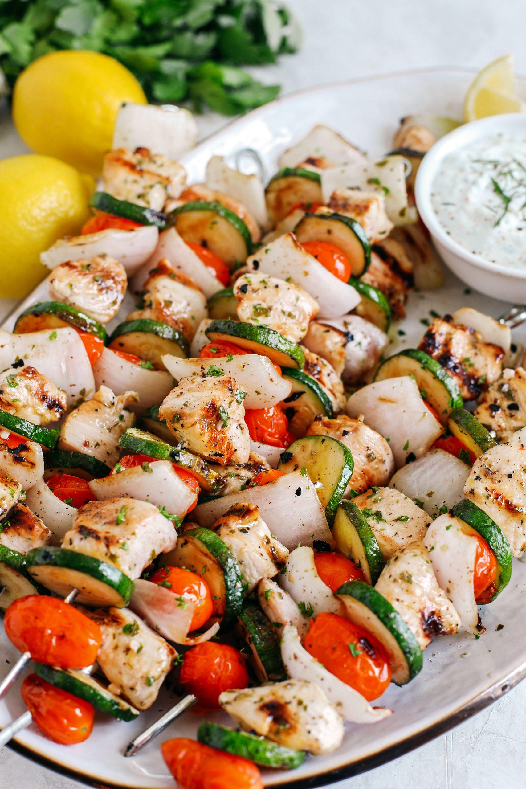 Espetinhos de frango grego super saborosos marinados com suco de limão picante, alho e ervas frescas e servidos com o mais delicioso molho tzatziki caseiro!