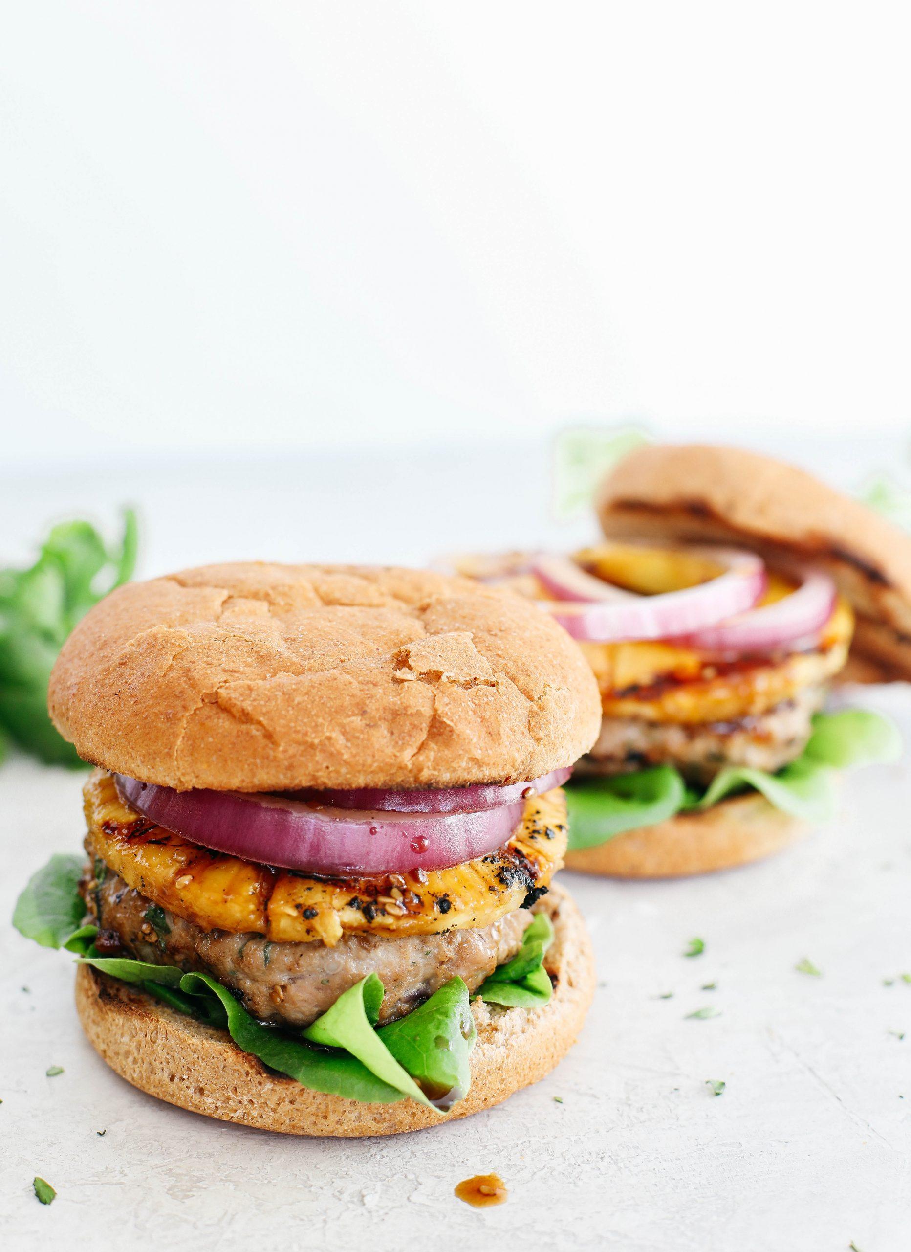 Esses deliciosos hambúrgueres de peru havaiano são embalados com toneladas de sabor, feitos com um molho teriyaki caseiro saudável e coberto com abacaxi fresco grelhado!