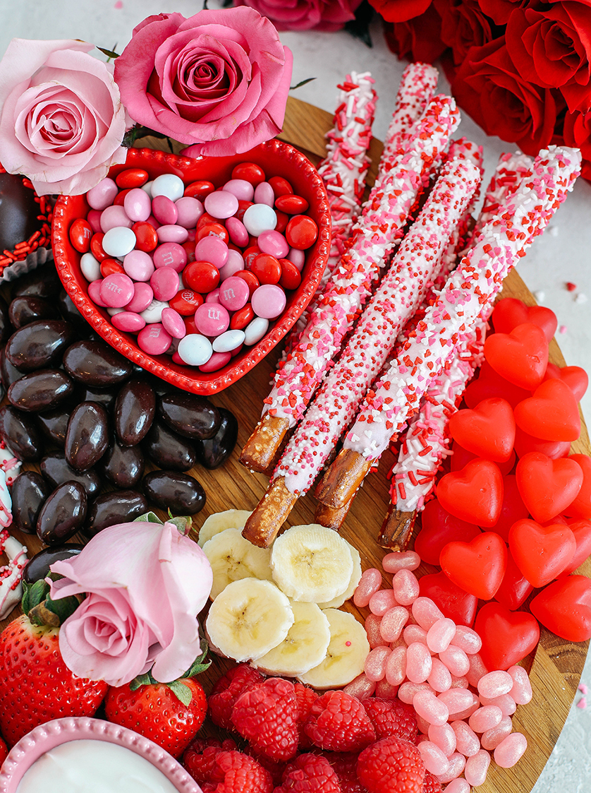 Celebrate Valentine's Day with a fun and festive dessert board made with healthier options like yogurt-dipped pretzels, chocolate covered almonds, fresh fruit and a honey yogurt dipping sauce!