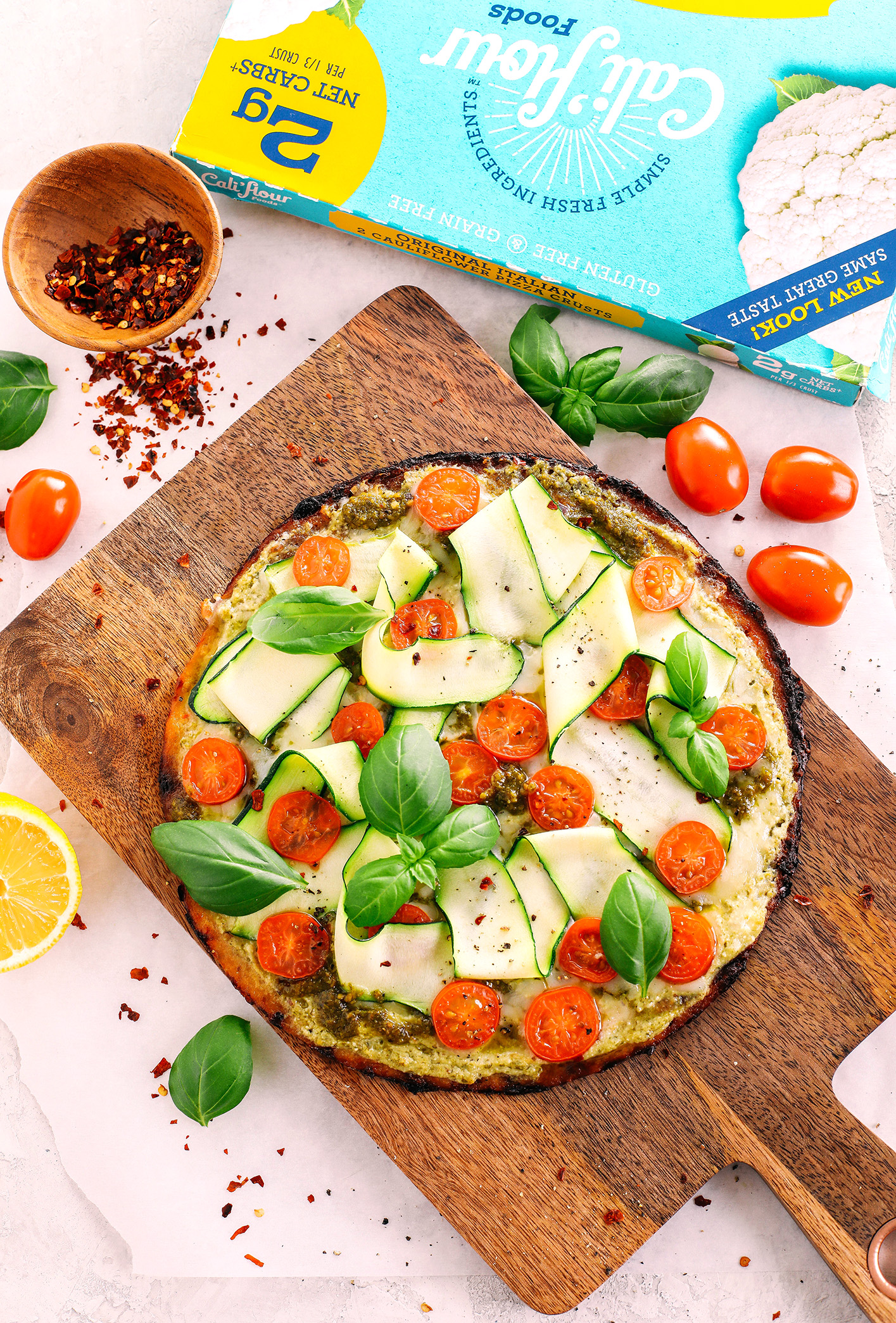 Garden Pesto Cauliflower Pizza loaded with fresh tomatoes, zucchini, homemade basil pesto and ricotta all topped on a crispy cauliflower crust for a delicious low carb meal in just 15 minutes!