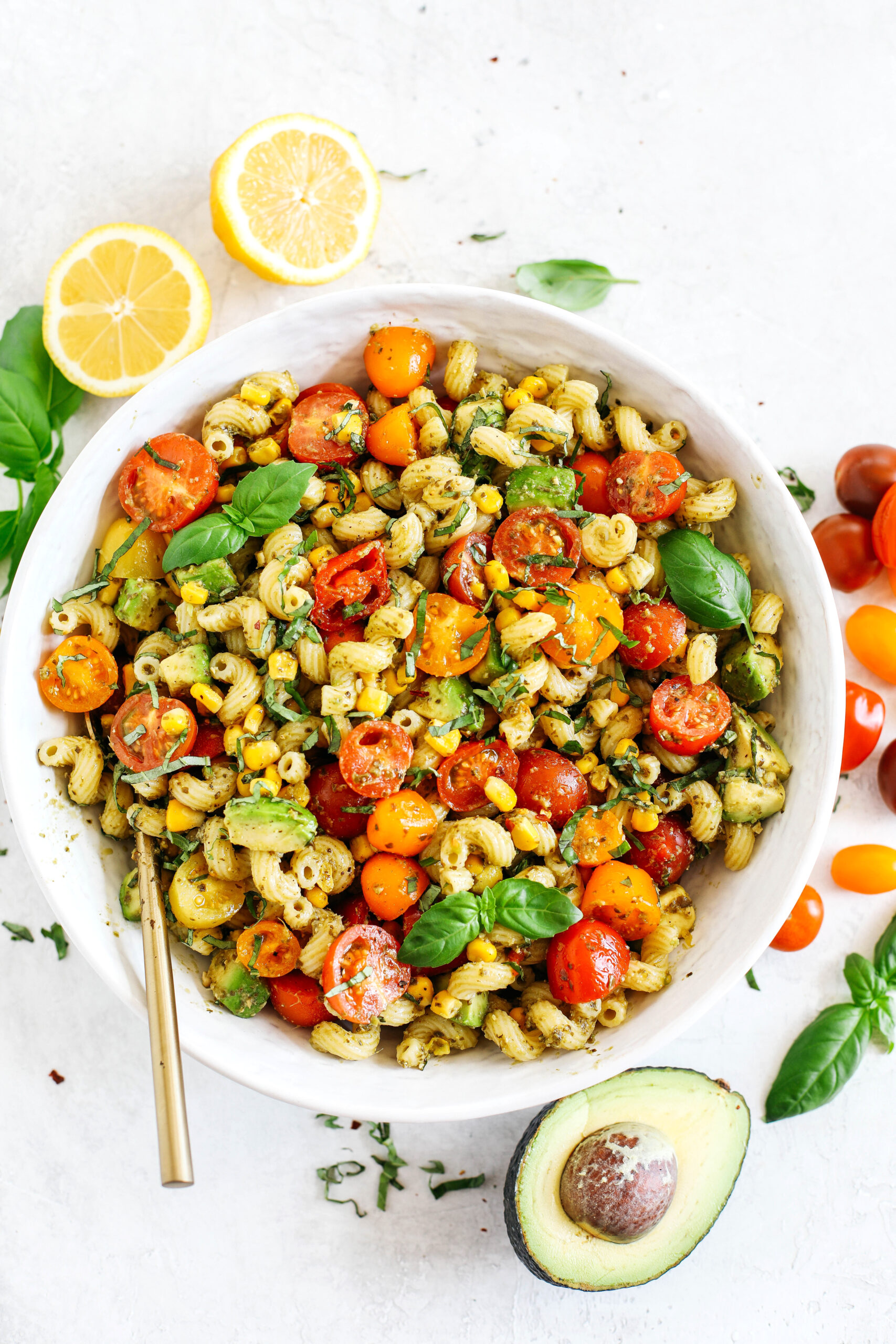 This EASY 10-minute Summer Pesto Pasta Salad is loaded with fresh ingredients like juicy tomatoes, corn, avocado, garlic, and lemon zest, all tossed together with warm pasta and delicious basil pesto!
