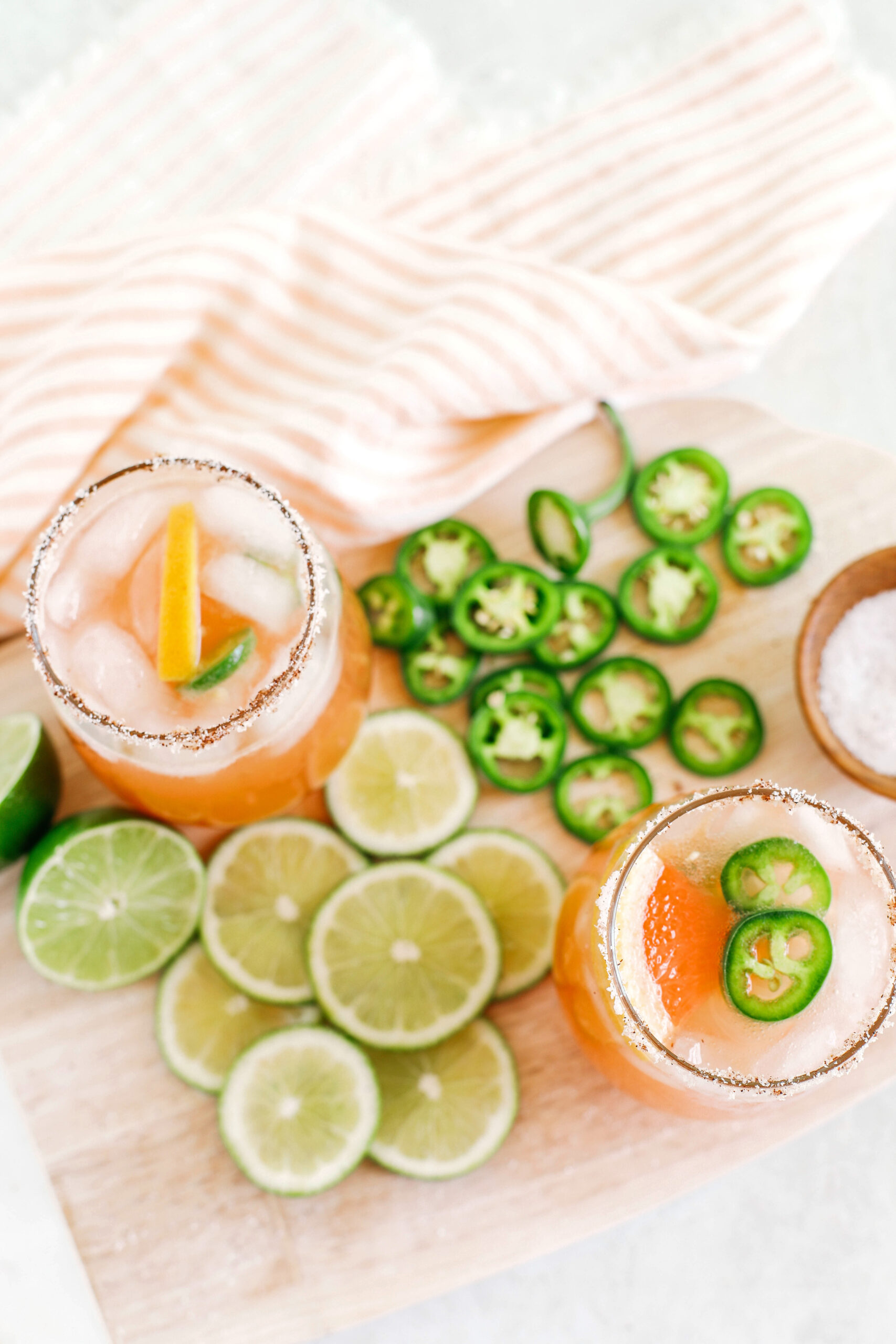 This Spicy Grapefruit Paloma is the perfect summer cocktail made with fresh limes and grapefruit, your favorite tequila, sparkling water, and my sweet and spicy jalapeño honey simple syrup!