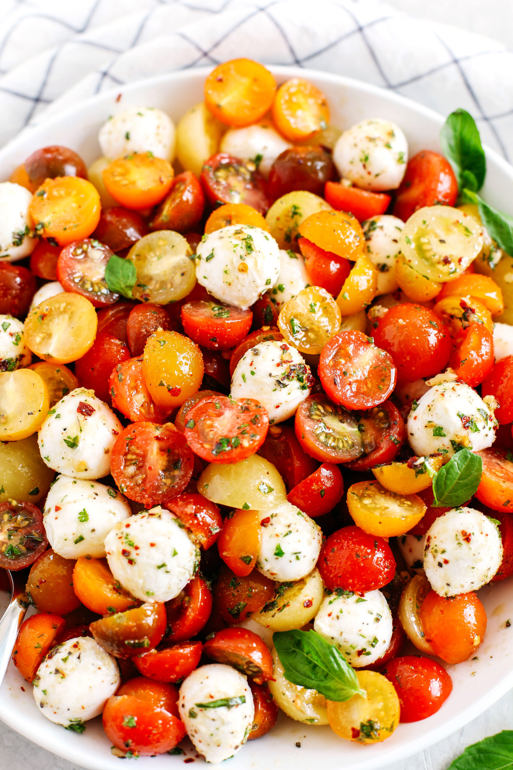 This Summer Caprese Salad is loaded with juicy tomatoes and creamy balls of mozzarella cheese all marinated in a delicious combination of olive oil, balsamic vinegar, garlic and fresh herbs!