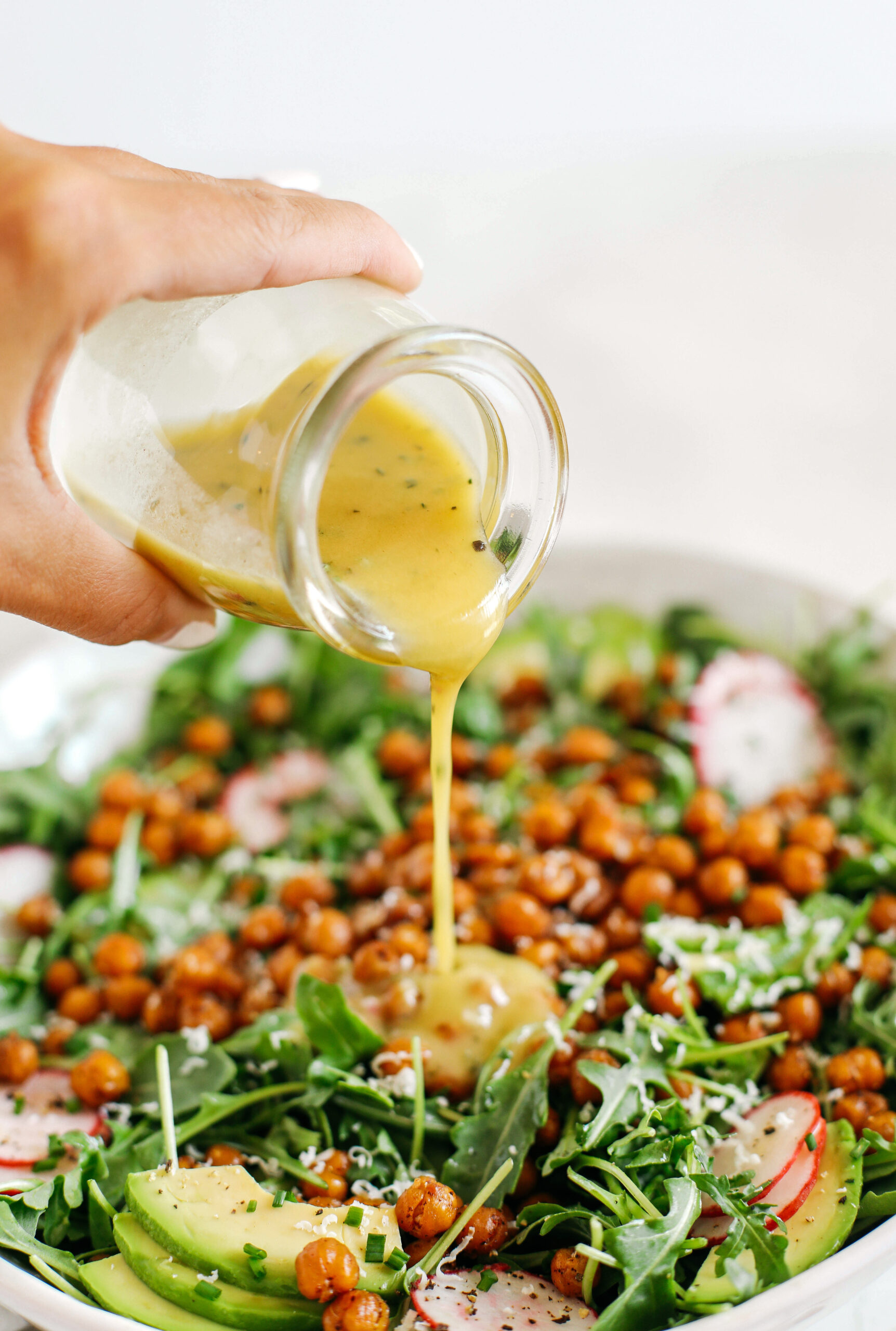 The most delicious Arugula Salad with Honey Roasted Chickpeas that are sweet, savory and perfectly crunchy! Top with fresh veggies, avocado slices and my lemon dijon herb dressing!