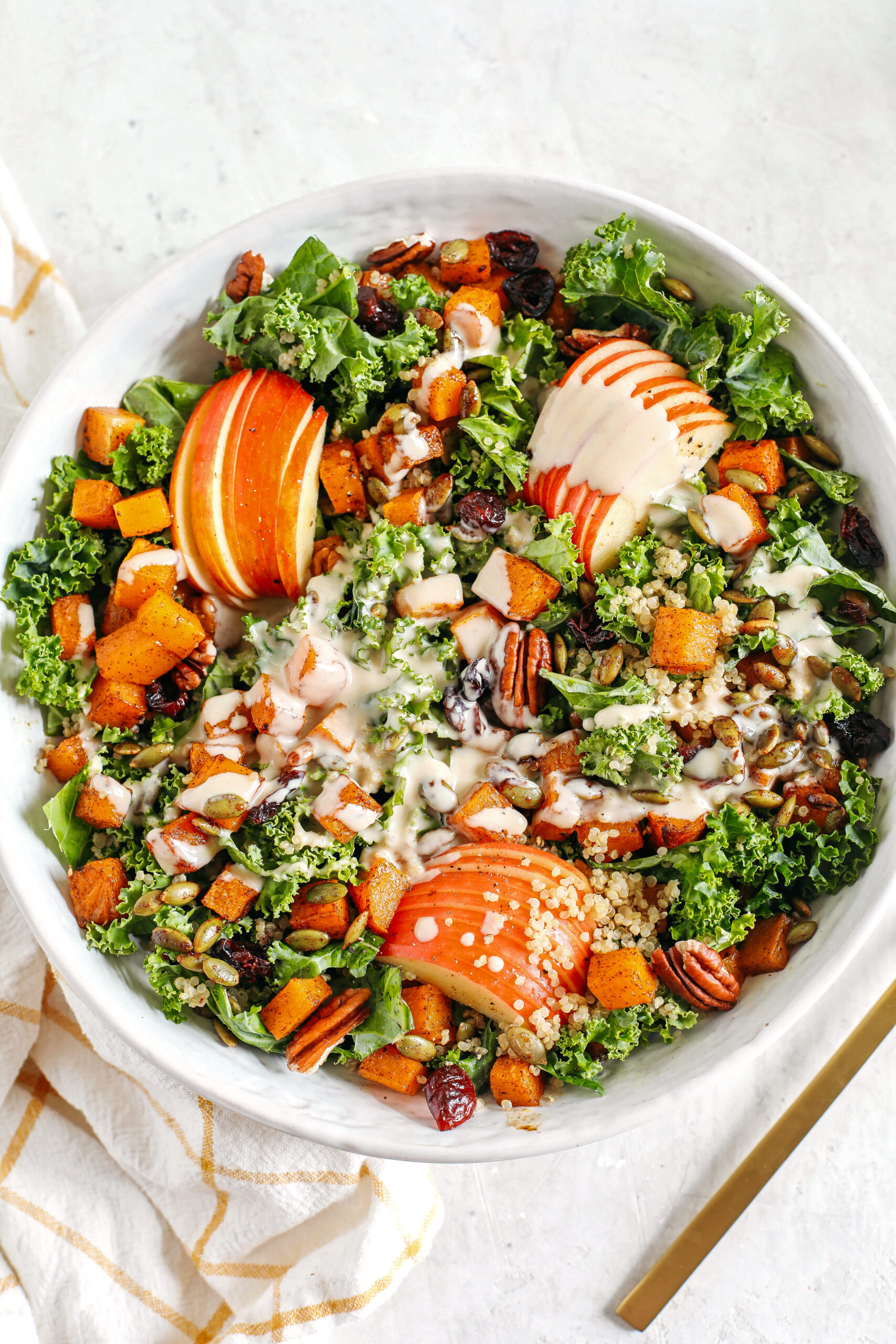The ultimate powerhouse Fall Salad made with leafy kale, protein-packed quinoa, sliced apples, roasted butternut squash, and spiced pepitas and pecans, all drizzled in the most delicious maple tahini dressing!